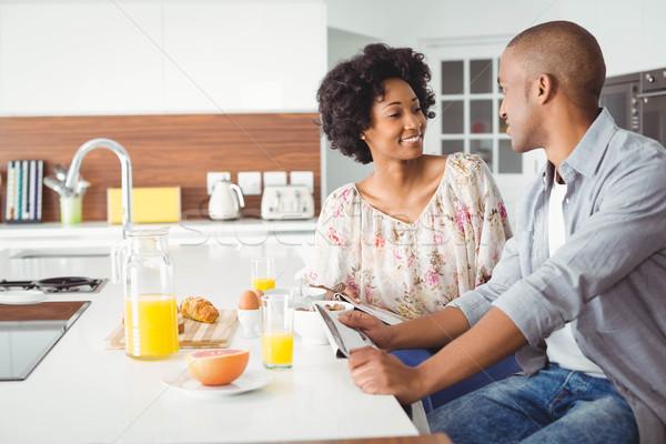 Sorridente casal alimentação café da manhã juntos cozinha Foto stock © wavebreak_media