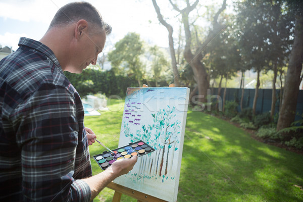 Man painting on canvas in garden Stock photo © wavebreak_media