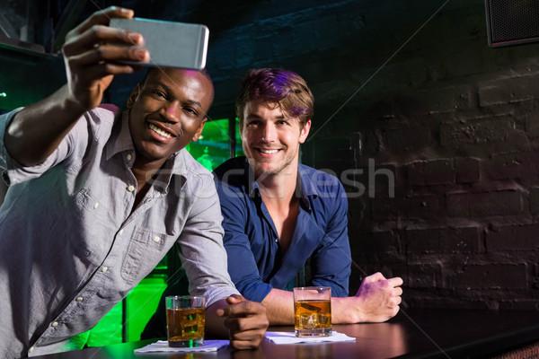 Dos hombres toma teléfono bar contra feliz Foto stock © wavebreak_media