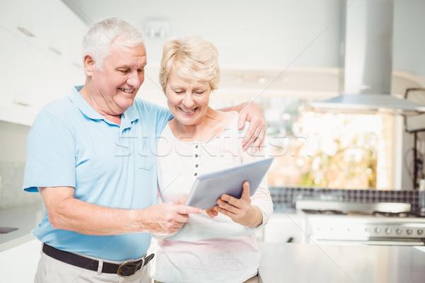 Happy senior couple holding digital tablet Stock photo © wavebreak_media