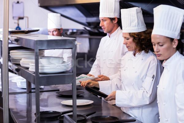 Team of chefs arranging plates on the order station Stock photo © wavebreak_media
