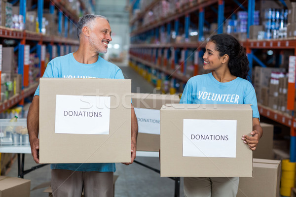 Happy volunteers are holding donations boxes and looking each ot Stock photo © wavebreak_media