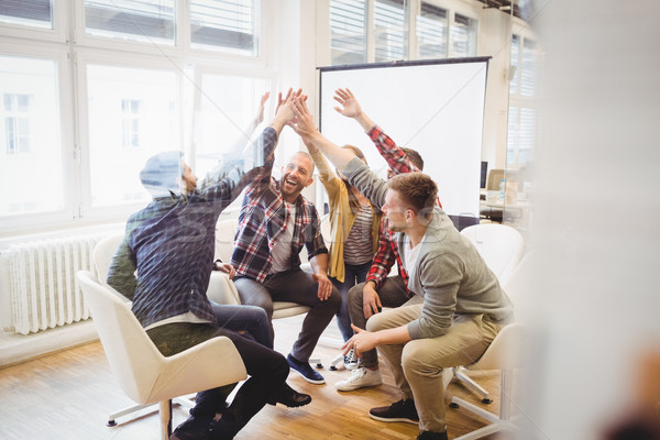 Creative business people giving high-five in meeting room Stock photo © wavebreak_media