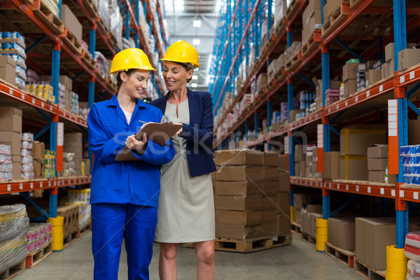 Warehouse manager and worker discussing with clipboard Stock photo © wavebreak_media