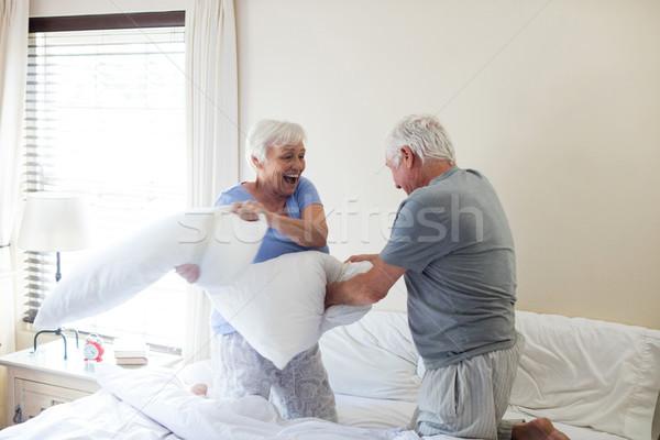 Pareja de ancianos pelea de almohadas cama dormitorio mujer feliz Foto stock © wavebreak_media