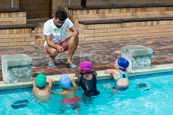 Instructor advising little swimmers at poolside Stock photo © wavebreak_media