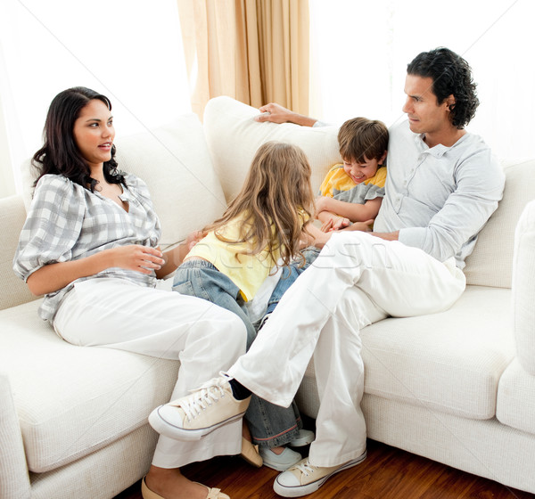 Attentive parents sitting on sofa with their children Stock photo © wavebreak_media