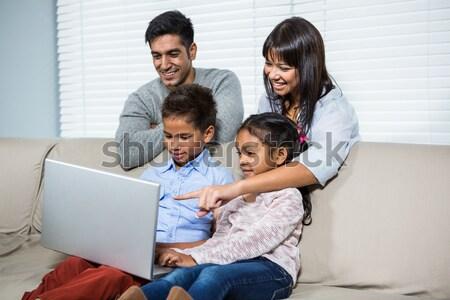 Glad family using a laptop sitting on sofa at home Stock photo © wavebreak_media