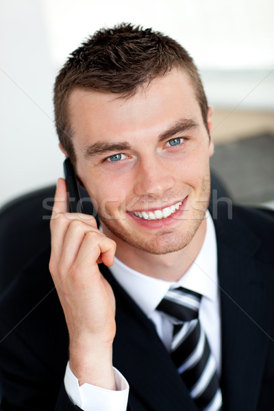 Stock photo: Smiling businessman using mobile phone in office