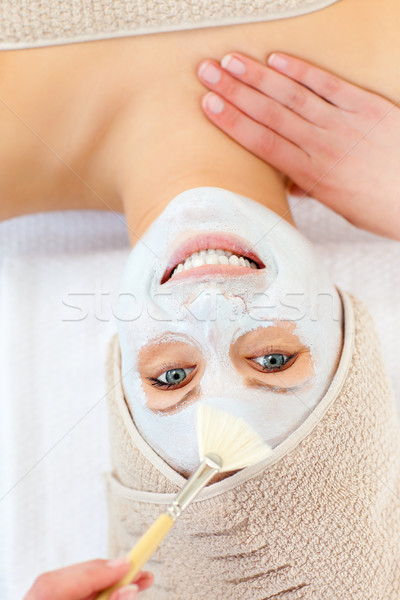 Glowing young woman receiving white cream on her face Stock photo © wavebreak_media
