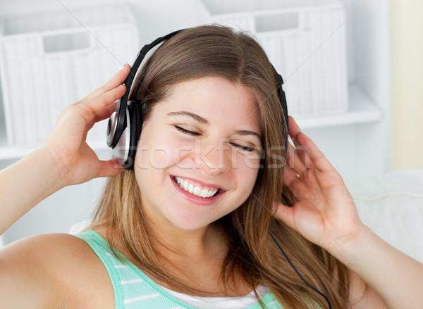Vrolijk jonge vrouw luisteren naar muziek hoofdtelefoon sofa home Stockfoto © wavebreak_media