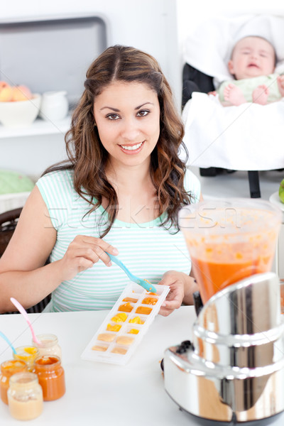 Caring mother preparing food for her lovely baby in the kitchen at home Stock photo © wavebreak_media