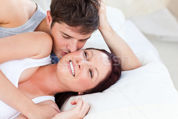 Caring caucasian couple lying on bed in the bedroom at home Stock photo © wavebreak_media