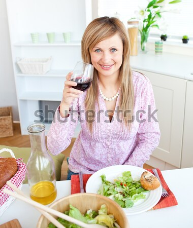 Portrait of a happy woman showing glass of red wine to the camera sitting in the kitchen Stock photo © wavebreak_media