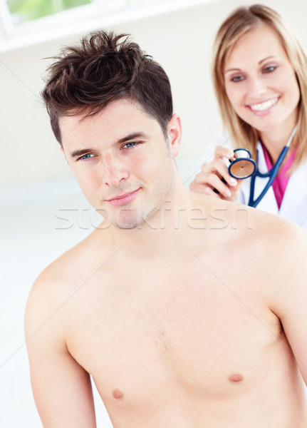 Cute female doctor feeling the breathing of a patient using her stethoscope in her office Stock photo © wavebreak_media