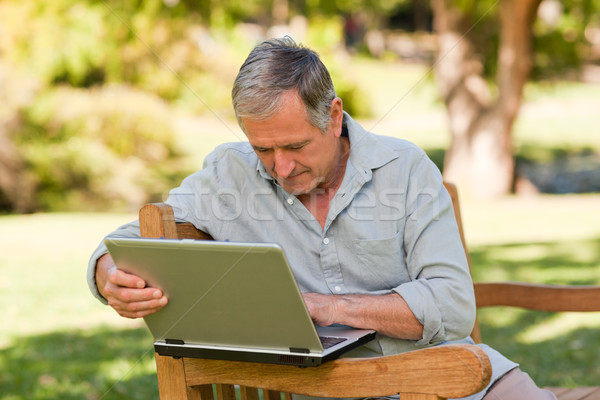 Retired man working on his laptop in the park Stock photo © wavebreak_media