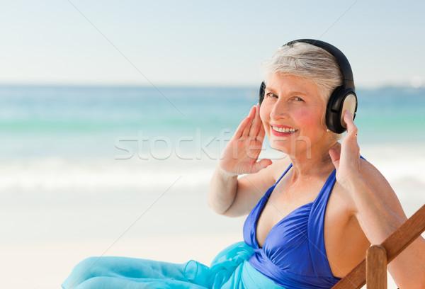 Pensione donna ascoltare musica spiaggia acqua felice Foto d'archivio © wavebreak_media