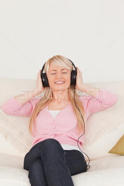 Zenét hallgat fejhallgató ül kanapé nappali nő Stock fotó © wavebreak_media