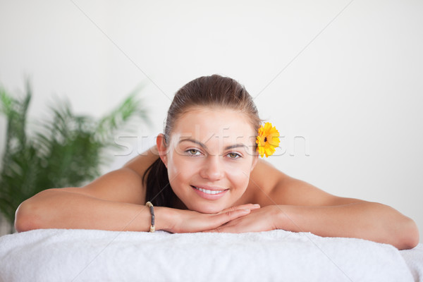 Stock photo: Smiling brunette with a flower on her ear in a spa
