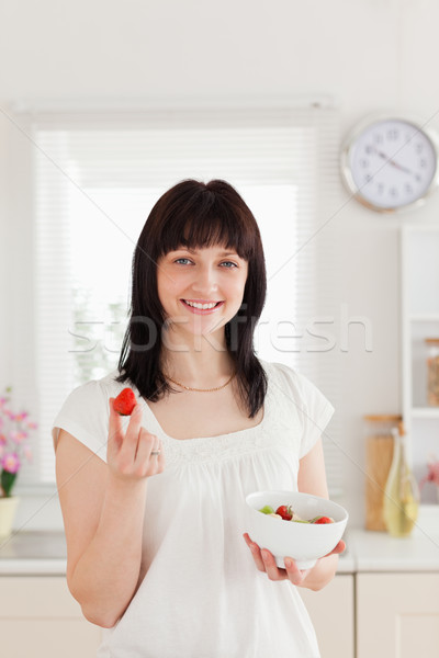 Pretty brunette female eating a cherry tomato while holding a bowl of vegetables in the kitchen Stock photo © wavebreak_media