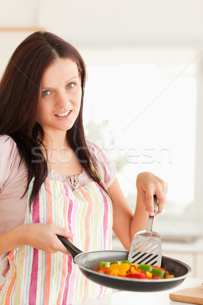 A woman in the kitchen is frying vegetables in a frying pan Stock photo © wavebreak_media