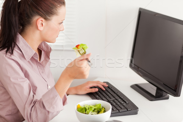 A businesswoman eats salad in her office whilst typing Stock photo © wavebreak_media