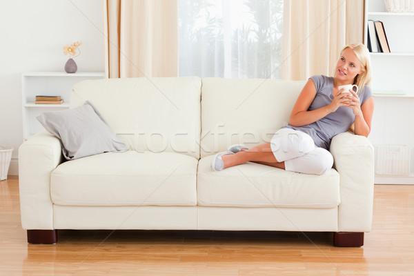 Träumen Frau halten Tasse Kaffee Wohnzimmer Stock foto © wavebreak_media
