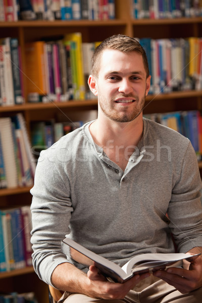 Portrait of a male student holding a book in a library Stock photo © wavebreak_media