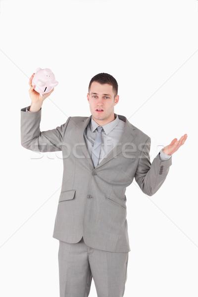 Portrait of a broke businessman shaking an empty piggy bank against a white background Stock photo © wavebreak_media