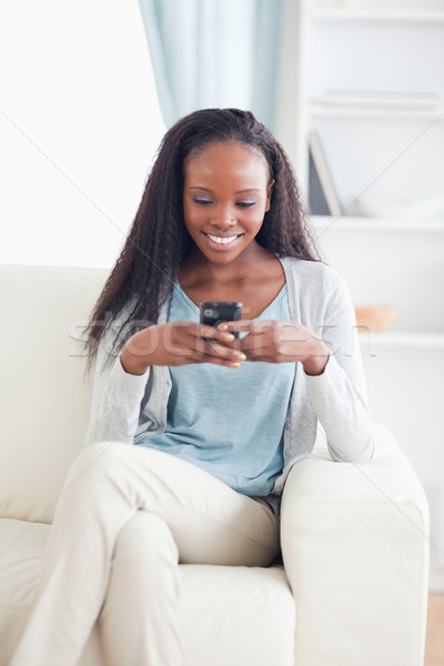 Smiling woman in living room text messaging Stock photo © wavebreak_media