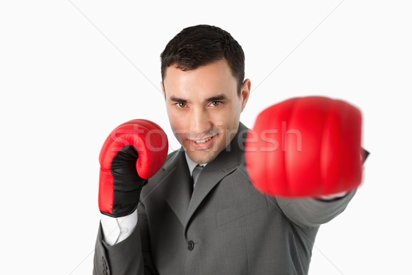 Businessman with boxing gloves on beating against a white background Stock photo © wavebreak_media
