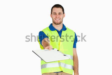 Smiling young delivery man asking for signature on delivery bill against a white background Stock photo © wavebreak_media