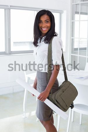 Smiling young woman sitting on her suitcase against a white background Stock photo © wavebreak_media