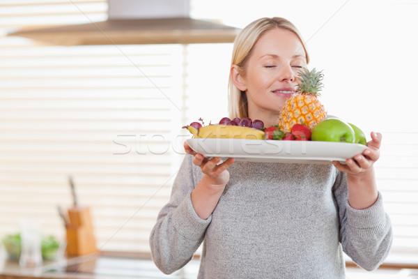 Smiling woman smelling on her fruit plate Stock photo © wavebreak_media