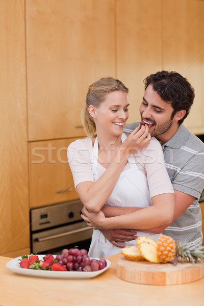 Portrait of a young couple eating fruits in their kitchen Stock photo © wavebreak_media