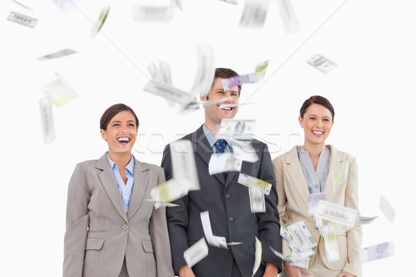 Money dropping down on smiling businessteam against a white background Stock photo © wavebreak_media