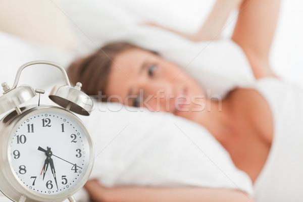 A woman blocks her ears with a pillow as her alarm clock goes off. Stock photo © wavebreak_media