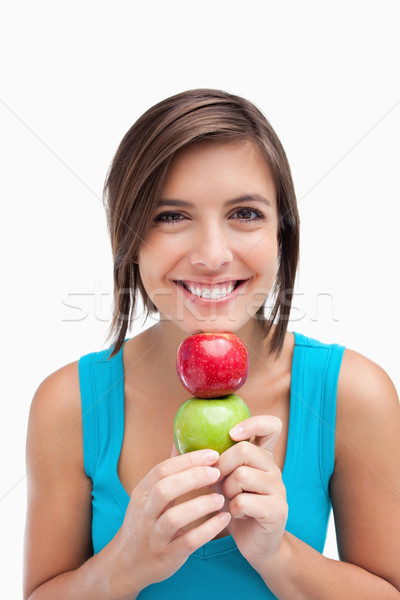 Young woman holding two apples between her hands and her chin Stock photo © wavebreak_media