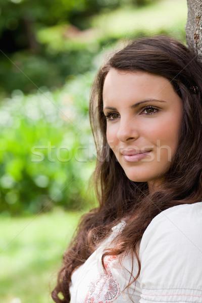 Fiatal békés nő dől fa másfelé néz Stock fotó © wavebreak_media