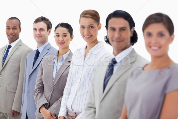 Close-up of smiling people dressed in suits looking straight with focus on the last three people Stock photo © wavebreak_media