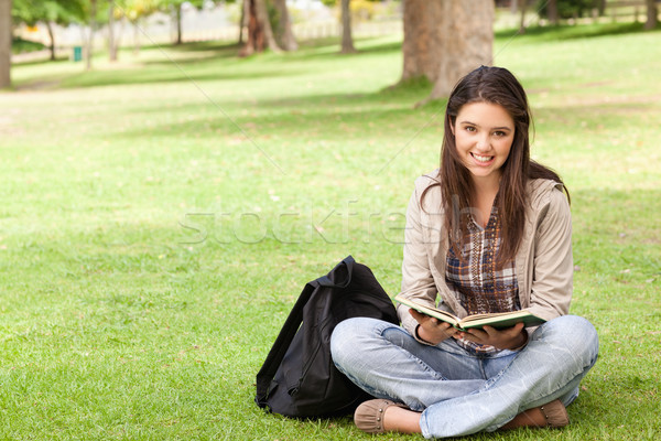 Smiling teenager sitting while holding a textbook in a park Stock photo © wavebreak_media