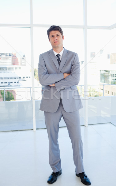 Businessman crossing his arms and standing upright in front of a bright window Stock photo © wavebreak_media