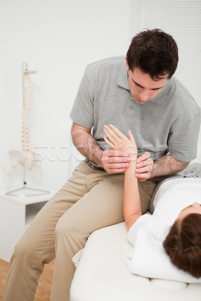 Physiotherapist placing his fingers on the hand of a patient in a room Stock photo © wavebreak_media