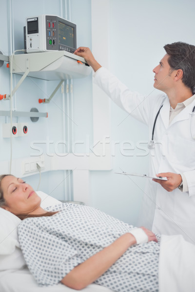 Doctor adjusting a monitor in hospital ward Stock photo © wavebreak_media