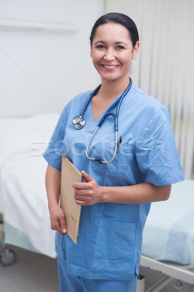 Smiling nurse holding a medical chart in hospital ward Stock photo © wavebreak_media