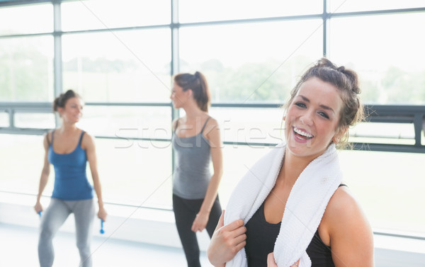 Woman smiling in fitness studio with towel around neck Stock photo © wavebreak_media
