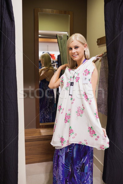Woman standing on the changing room holding up dress Stock photo © wavebreak_media