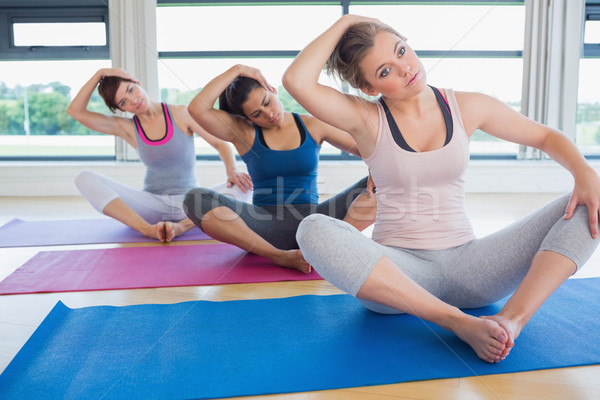 Women stretching in bound angle yoga pose in fitness studio Stock photo © wavebreak_media