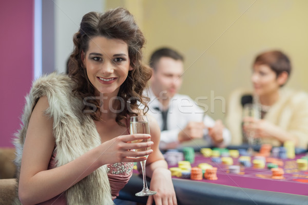 Woman with champagne smiling at roulette table Stock photo © wavebreak_media