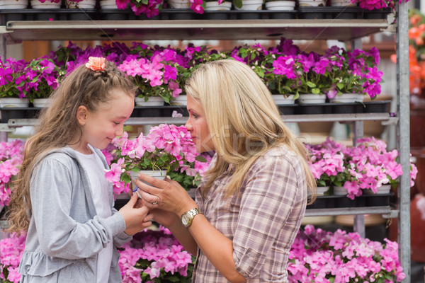 Maothe and daughter smelling plant in garden center Stock photo © wavebreak_media